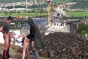 Cute little chick fucked in public construction site by 2 guys with big dicks